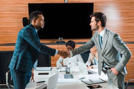 Photo pour Deux beaux hommes d'affaires serrent la main alors qu'ils se tiennent près de collègues multiculturels dans la salle de conférence - image libre de droit