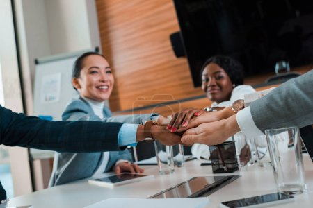 Photo pour Focus sélectif of young multicultural business people holding joined hands while sitting at desk in conference hall, cropped view - image libre de droit