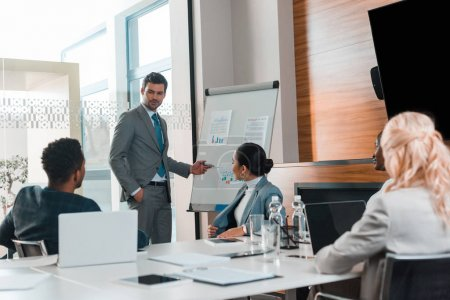Photo for Multicultural businesspeople looking at young businessman pointing with hand at flipchart with infographics - Royalty Free Image