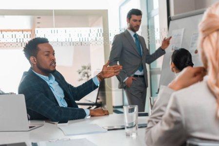 Photo pour Bel homme d'affaires pointant du doigt sur un tableau à feuilles mobiles avec infographie tandis que des collègues multiculturels discutent dans une salle de conférence - image libre de droit