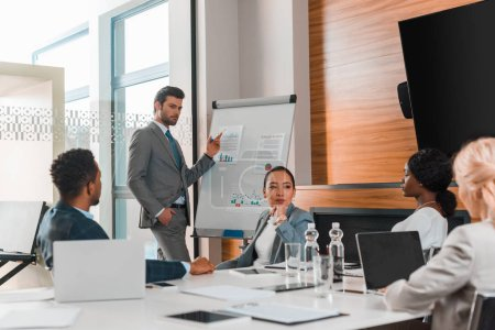 Photo for Handsome businessman pointing with finger at flipchart with infographics while multicultural colleagues sitting at desk in conference hall - Royalty Free Image