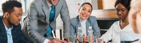 Photo for Cropped view of young businessman standing near smiling multicultural colleagues sitting at desk in conference hall, panoramic shot - Royalty Free Image
