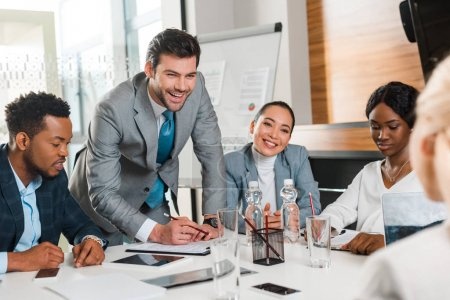 Photo pour Focalisation sélective d'un homme d'affaires gai tenant un crayon tout en se tenant près de collègues multiculturels assis à son bureau dans la salle de conférence - image libre de droit