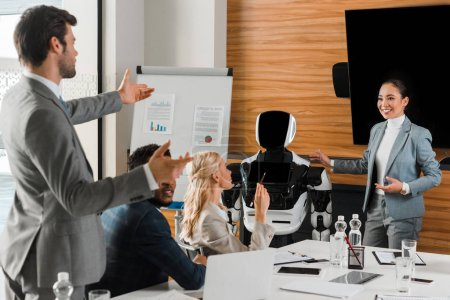 Photo pour Attractive asian business woman pointing with hands at robot near colleagues in conference hall - image libre de droit