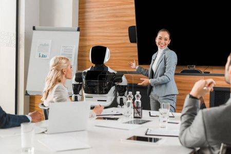 Photo pour Une femme d'affaires asiatique souriante pointant des mains vers un robot pendant qu'elle parle à des collègues dans une salle de conférence - image libre de droit