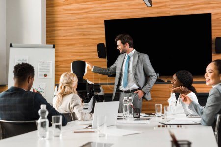 handsome businessman showing robot to multicultural colleagues sitting in conference hall