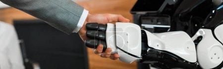 Photo pour Vue partielle d'un homme d'affaires et d'un robot serrant la main au bureau, photo panoramique - image libre de droit