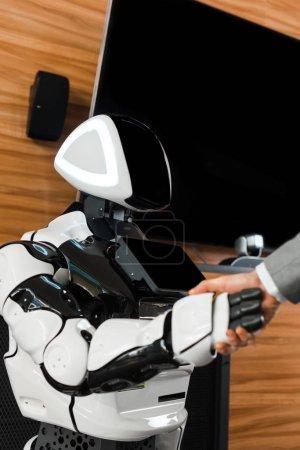 Photo pour Vue partielle d'un homme d'affaires serrant la main avec un robot humanoïde au bureau - image libre de droit