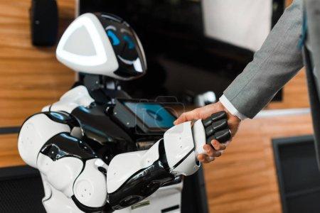 Photo pour Crochet vue d'un homme d'affaires serrant la main avec un robot souriant au bureau - image libre de droit