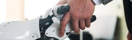 Photo pour Crochet vue d'un homme d'affaires et d'un robot serrant la main au bureau, photo panoramique - image libre de droit
