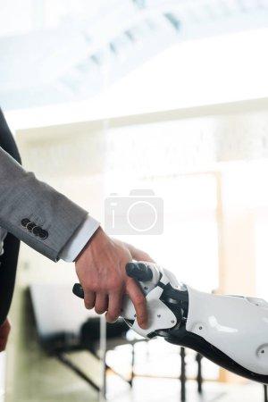 Photo pour Vue partielle d'un homme d'affaires et d'un robot serrant la main au bureau - image libre de droit
