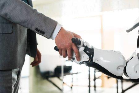 Photo pour Crochet vue d'un homme d'affaires et d'un robot serrant la main au bureau - image libre de droit