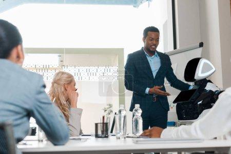 Photo pour Homme d'affaires afro-américain souriant montrant robot à des collègues multiculturels dans la salle de conférence - image libre de droit