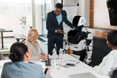 Photo pour Bel homme d'affaires afro-américain pointant du doigt robot près de collègues multiculturels dans la salle de conférence - image libre de droit