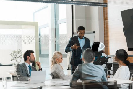 handsome african american businessman showing robot to multicultural colleagues in office
