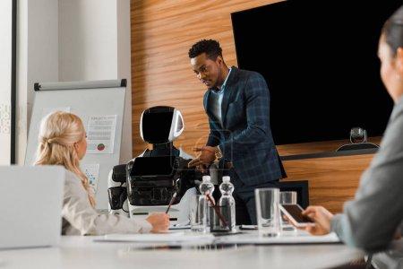 Photo pour Bel homme d'affaires afro-américain pointant du doigt robot près de collègues dans la salle de conférence - image libre de droit