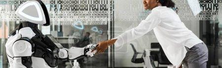 Photo pour Photo panoramique d'une femme d'affaires africaine américaine serrant la main d'un robot au bureau - image libre de droit