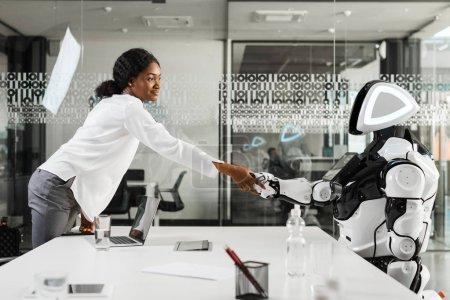 Photo pour Une femme d'affaires africaine américaine souriante serrant la main d'un robot au bureau - image libre de droit