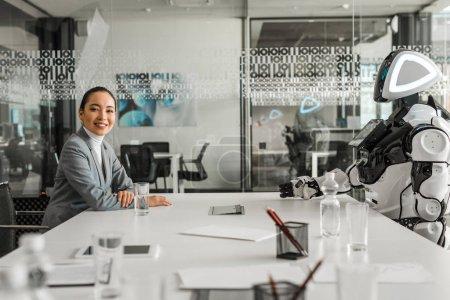 Photo pour Point de mire sélectif d'une femme d'affaires asiatique souriante regardant la caméra alors qu'elle est assise près d'un robot - image libre de droit