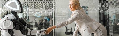 Photo pour Photo panoramique femme d'affaires souriante serrant la main d'un robot assis à un bureau dans une salle de réunion - image libre de droit