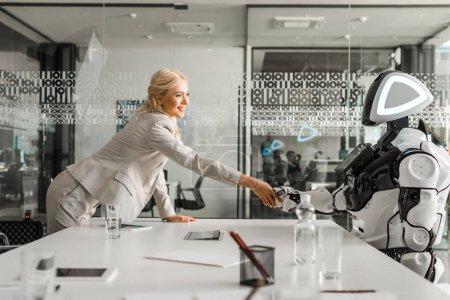 Photo pour Une femme d'affaires souriante serrant la main d'un robot assis à son bureau dans une salle de réunion - image libre de droit