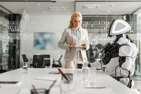 Photo for Attractive businesswoman using digital tablet while standing near robot in meeting room - Royalty Free Image
