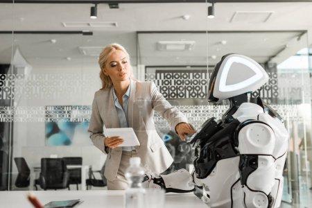 Photo pour Séduisante femme d'affaires tenant une tablette numérique en utilisant un robot - image libre de droit