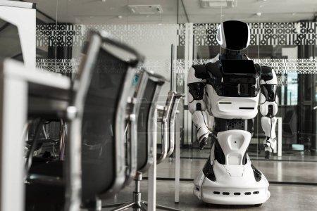 Photo pour Focus sélectif du robot humanoïde debout dans la salle de conférence du bureau moderne - image libre de droit