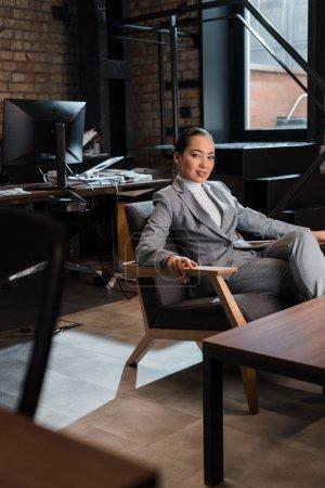 Foto de Hermosa asiático mujer de negocios sentado en sillón y sonriendo a cámara - Imagen libre de derechos