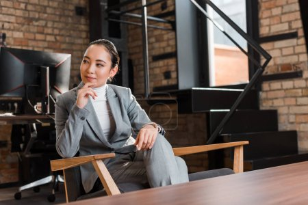 Photo pour Attractive asian business woman sitting in armchair and touching chin while looking away - image libre de droit