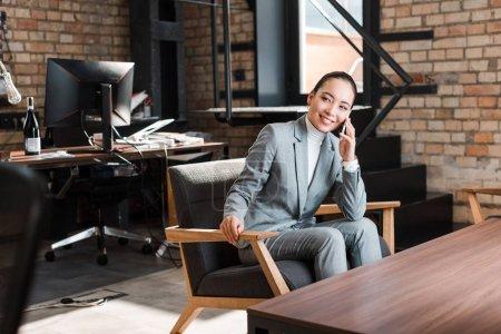 Photo pour Joyeuse femme d'affaires asiatique assise dans un fauteuil et parlant sur un téléphone intelligent - image libre de droit