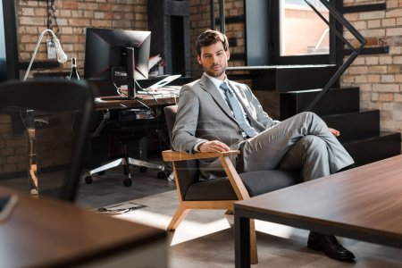 Photo for Confident, handsome businessman sitting in armchair and looking at camera - Royalty Free Image