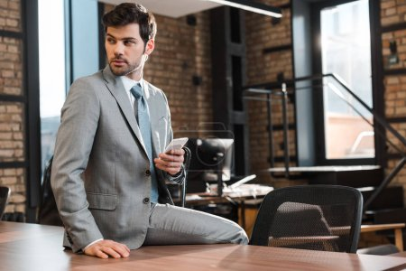 Photo for Confident, handsome businessman sitting on office desk, holding smartphone and looking away - Royalty Free Image