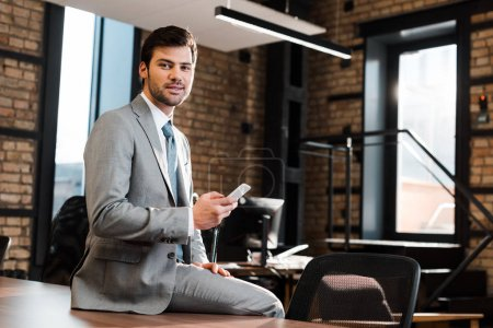 Photo for Handsome, positive businessman sitting on office desk, holding smartphone and looking at camera - Royalty Free Image