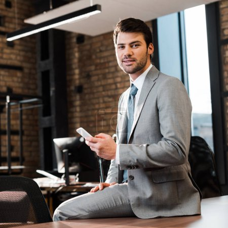 Photo for Handsome, smiling businessman sitting on office desk, holding smartphone and looking at camera - Royalty Free Image