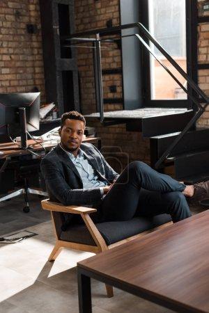 красивый, уверенный в себе африканский бизнесмен сидит в кресле и смотрит в камеру