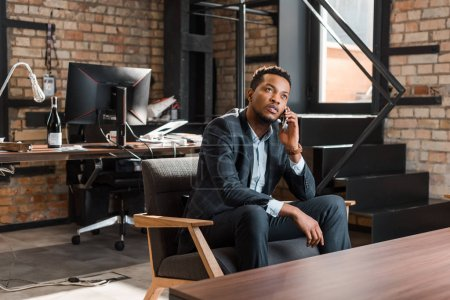 Photo for Thoughtful african american businessman sitting in armchair and looking up while talking on smartphone - Royalty Free Image