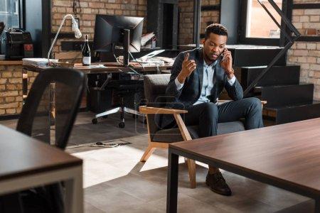 Photo pour Homme d'affaires afro-américain sérieux assis dans un fauteuil et montrant geste idée tout en parlant sur smartphone - image libre de droit