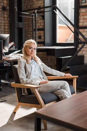 attractive, pensive businesswoman sitting in armchair and looking at camera