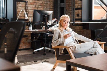 attraktive konzentrierte Geschäftsfrau sitzt im Sessel und plaudert auf dem Smartphone