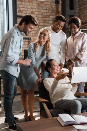 cheerful multicultural businesspeople standing near happy asian colleague using laptop