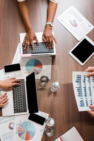 Photo pour Des gens d'affaires multiculturels qui travaillent avec des ordinateurs portatifs et des documents, vue de haut - image libre de droit