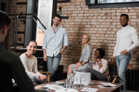 young multicultural businesspeople smiling during meeting in office