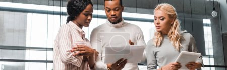 Photo for Panoramic shot of young multicultural businesspeople talking while looking at documents - Royalty Free Image