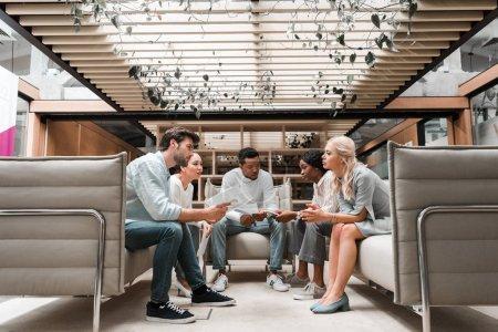Foto de Jóvenes empresarios multiculturales sentados en el salón de oficinas durante las reuniones - Imagen libre de derechos