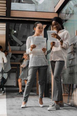 Photo pour Femmes d'affaires africaines d'Amérique et d'Asie concentrées avec tablette numérique et documents se présentant au pouvoir avec collègues multiculturels sur le fond - image libre de droit