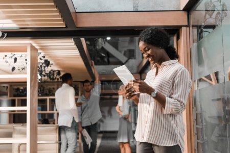 Photo pour Femme d'affaires afro-américaine joyeuse utilisant une tablette numérique tout en collègues multiculturels debout sur fond - image libre de droit