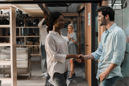 Photo for Happy african american businesswoman shaking hands with smiling colleague in office - Royalty Free Image