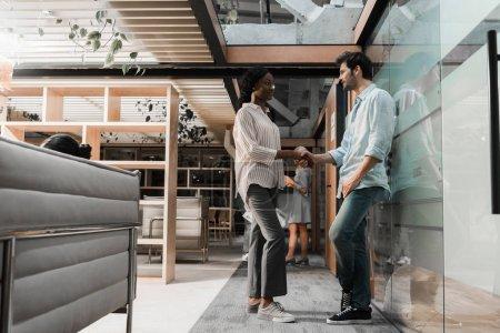 Foto de Jovencita empresaria afriamericana estrechando la mano con un colega guapo. - Imagen libre de derechos