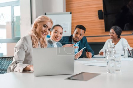 Photo for Smiling multicultural businesspeople sitting in conference hall and looking at laptop - Royalty Free Image